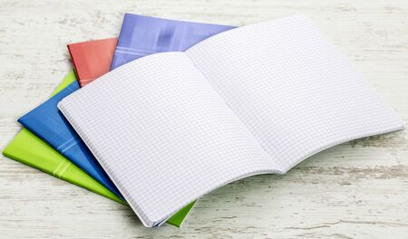 a study: Image of a stack of colorful notebooks on a white wooden table.