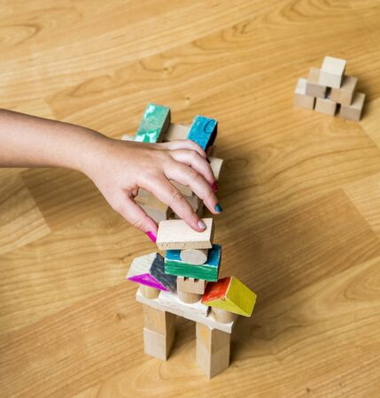 play room: Upper view of a little girls hand building something using wooden geometrical pieces, in her play room. Stock Photo