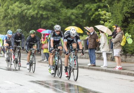 12 step: Gerardmer, France - July 12, 2014: Group of cyclists including Mark Renshaw of Team Omega Pharma-Quick Step, riding during a rainy day in the stage 8 of Le Tour de France 2014 in Gerardmer.