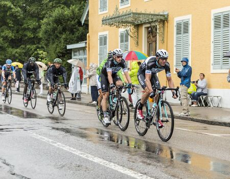 12 step: Gerardmer, France - July 12, 2014: Group of cyclists including Mark Renshaw and Alessandro Petacchi of Team Omega Pharma-Quick Step, riding during a rainy day in the stage 8 of Le Tour de France 2014 in Gerardmer.