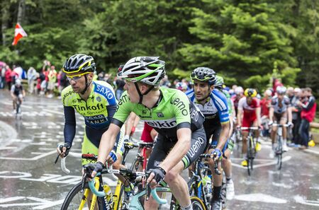 sergio: Le Markstein, France- July 13, 2014:Group of cyclists, inside the peloton,climbing the difficult road to mountain pass Le Markstein in Vosges Mountains,during the stage 9 of Le Tour de France 2014.