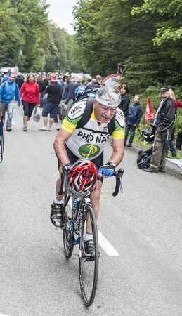 mountain bicycling: Le Markstein, France- July 13, 2014: Old amateur climbing the road to the mountain pass Le Markenstein during the stage 9 of Le Tour de France 2014. Editorial