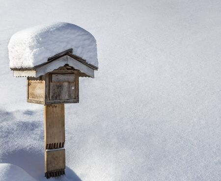 postmail: Wooden mailbox covered by snow in a courtyard in winter.