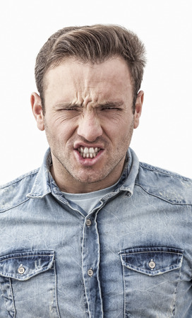 bluejeans: Portrait of a young angry man isolated against a white background.