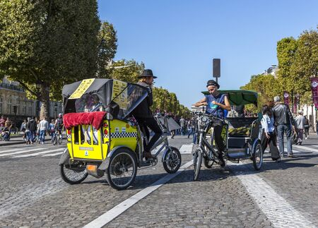 velo: Paris, France - September 27, 2015: Two drives of ecological touristic velo-vehicles have a discussion on Champs Elysees during the Day without cars held in some areas in Paris on September 27,2015.