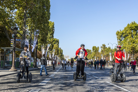 elysees: Paris,France - September 27, 2015: People walking and riding segways on Champs Elysees during the Day without cars held in some areas in Paris on September 27,2015.