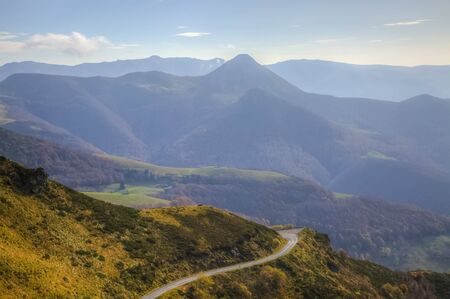 massif: Misty morning view of a scenic road located in the volcanic Central Massif in France. Stock Photo