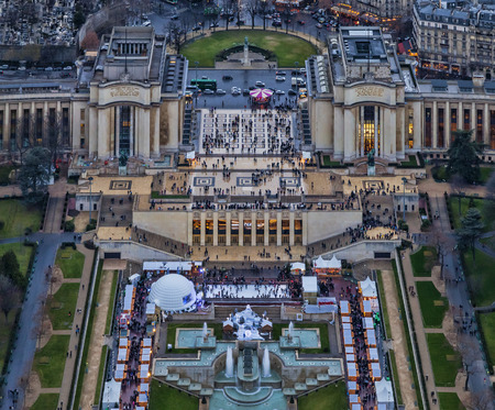 bir: Bird eye view over Trocadero and Palais de Chaillot with people walking between stands of Christmas Market in a winter evening in Paris. Stock Photo
