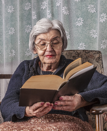 Portrait of an old woman reading a book. photo