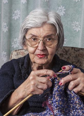 Portret van een oude gerimpelde vrouw breien in haar huis. Stockfoto