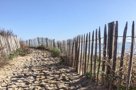 duna: Sendero entre las cercas de madera en la duna atlántica de Bretaña, en el noroeste de Francia.