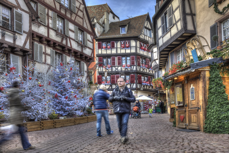 colmar: Colmar, France- Decmebr 06,2013: People walking in a town square between traditional half-timber houses and specific Christmas decoration in Colmar, Alsace, France. HDR image with selective motion blur on some of the people.  Editorial