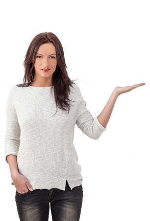 young add: Young smiling woman holding out her hand as if she were displaying something.You can add any text or object on the palm of her hand.