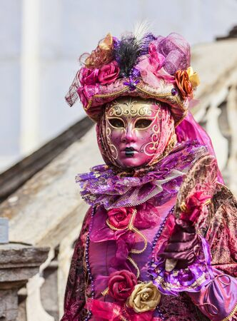 disguised: Annecy, France- February 24, 2013:Environmental portrait of an unidentified person disguised in a beautiful costume with a mirror in Annecy, France, during a Venetian Carnival, which is held yearly, to celebrate the beauty of the real Venice.