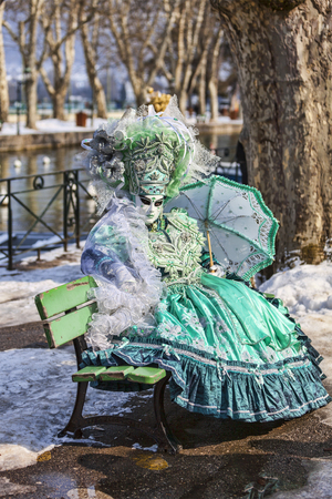 disguised: Annecy, France- February 24, 2013:Unidentified person disguised in a beautiful green costume sits on a bench in Annecy, France, during a Venetian Carnival, which is held yearly, to celebrate the beauty of the real Venice.