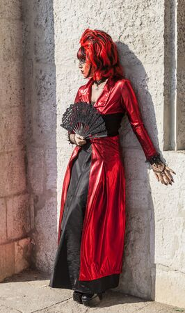 to conceal: Venice, Italy-February 18, 2012:Image of a person wearing a red and black disguise with a fan posing near a stone wall during The Venice Carnival days.
