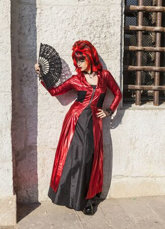 mardigras: Venice, Italy-February 18, 2012:Image of a person wearing a red and black disguise with a fan posing near a stone wall during The Venice Carnival days.