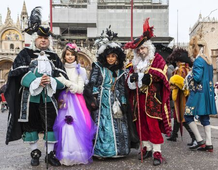 historical: Venice,Italy- March 2, 2014: Group of disguised people posing in San Marco Square during the Venice Carnival days.