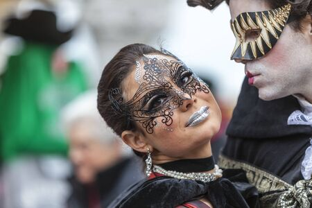 human lips: Venice,Italy- March 2, 2014: Portrait of a couple with Colombina masks and specific make-ups, posing in San Marco Square during the Venice Carnival days.