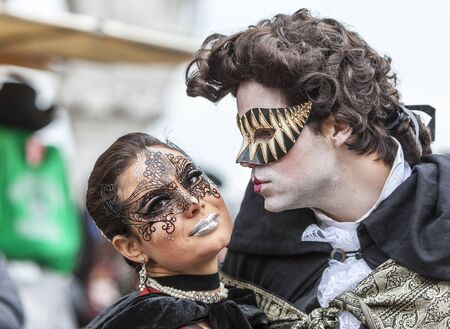romantic love: Venice,Italy- March 2, 2014: Portrait of a couple with Colombina masks and specific make-ups, posing in San Marco Square during the Venice Carnival days.