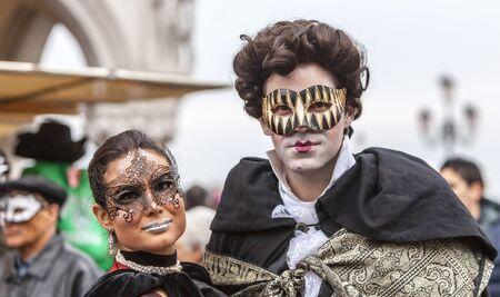 Venedig, Italien 2. März 2014: Portrait eines Paares mit Colombina Masken und spezifische Make-ups, während der Karneval von Venedig Tagen in San Marco Platz aufwirft.