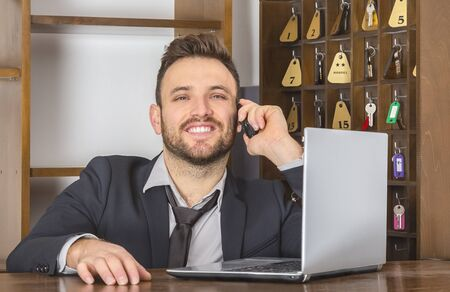 business support: Portrait of a smiling receptionist on the phone at his desk in a small hostel. Stock Photo