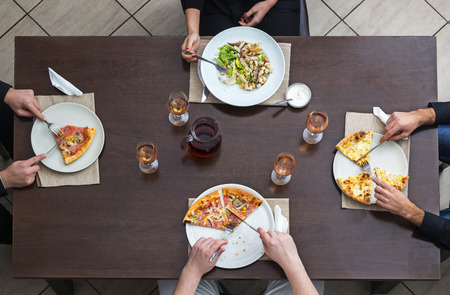 Vista dall'alto di amici che mangiano pizza e insalata su un tavolo woooden in un ristorante.