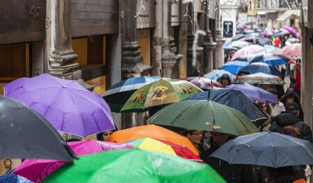 walking street: Venice,Italy- March 2, 2014: Crowd of people with umbrellas walking in the rain in a narrow Venetian street during the Venice Carnival days. Editorial