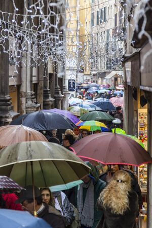 italy street: Venice,Italy- March 2, 2014: Crowd of people with umbrellas walking in the rain in a narrow Venetian street during the Venice Carnival days. Editorial