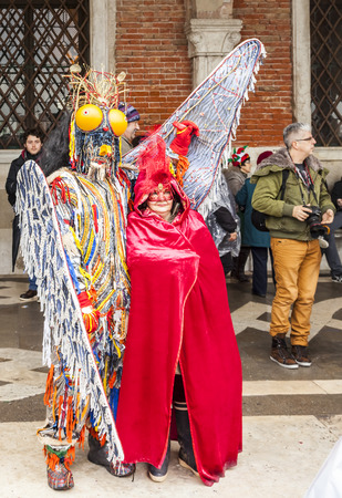 venice carnival: Venice,Italy- March 2, 2014: Couple disguised in colorful costumes, posing in San Marco Square during the Venice Carnival days.