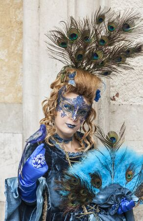 venice carnival: Venice,Italy- March 2, 2014: A woman disguised in blue costume with peacock feathers posing in San Marco Square during the Venice Carnival days.