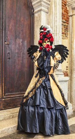 doges  palace: Venice,Italy- March 2, 2014: Unidentified person disguised in a black costume with a red rose posing near the walls of The Doges Palace in San Marco Sqaure during the Venice Carnival days.