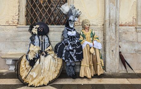Venice,Italy- March 2, 2014: Three unidentified persons wearing beautiful venetian costumes poses near the walls of The Doges Palace in San Marco Square during the Venice Carnival. Editorial