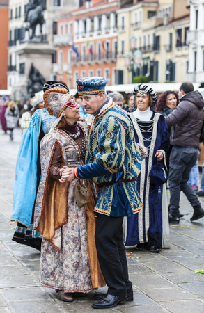 campanille: Venice, Italy- March 02, 2014: Unidentified happy couple wearing traditional clothes dance on Sestiere Castello in Venice during the Carnival days.