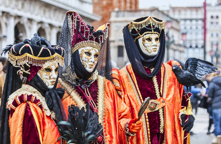 Venice,Italy- March 2, 2014: Portrait of three persons with Venetian masks in San Marco Square during the Venice Carnival days. Selective focus on the middle one.