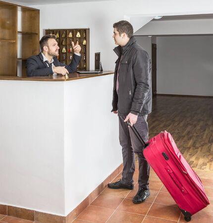 recepcionista: La recepcionista y un disucuss cliente en el mostrador de recepción del albergue. Foto de archivo