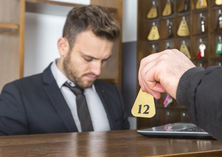 recepcionista: Imagen de la mano de un invitado que da la llave en la recepci�n del hotel. enfoque selectivo en la tecla. Foto de archivo