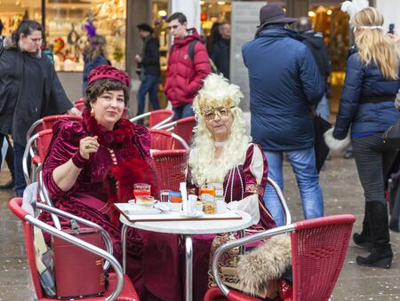 europe travel: Venice,Italy- March 2, 2014: Two ladies in traditional costumes enjoying a snack on a terrace in San Marco Square during the Venice Carnival days. Editorial