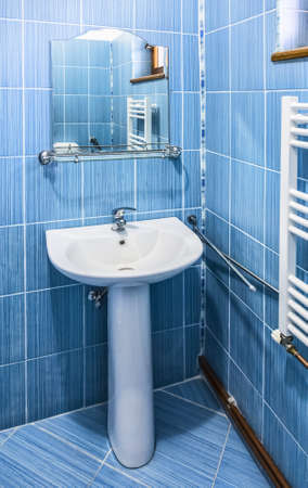 hostel: Interior of a blue bathroom with sink and mirror in a hostel. Stock Photo