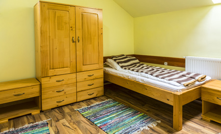 Clean hostel room with bed and wardrobe