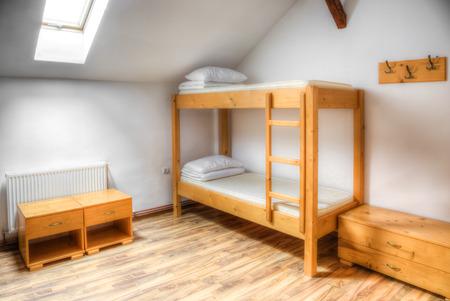habitación de un hostal limpio, con literas de madera. Foto de archivo
