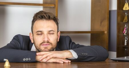 Portrait of a tired receptionist taking a nap at his desk at the hostel reception. Stock Photo