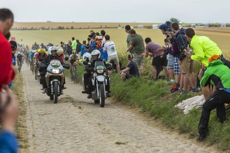 bystanders: Quievy,France - July 07, 2015: Two official bikes forego in front of the peloton on a cobblestone road during the stage 4 of Le Tour de France 2015 in Quievy, France, on 07 July,2015.