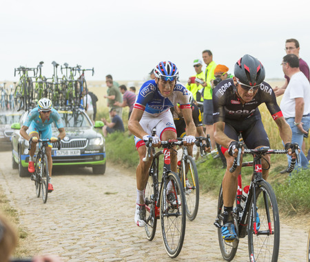 bystanders: Quievy,France - July 07, 2015: The French cyclist Matthieu Ladagnous of FDJ Team riding in the peloton on a cobblestone road during the stage 4 of Le Tour de France 2015 in Quievy, France, on 07 July,2015.