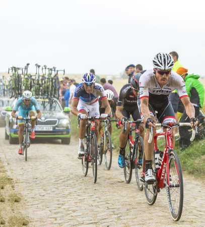 cobblestone road: Quievy,France - July 07, 2015: The Swiss cyclist Gregory Rast of Trek-Segafredo Team riding in the peloton on a cobblestone road during the stage 4 of Le Tour de France 2015 in Quievy, France, on 07 July,2015.