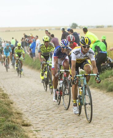 bystanders: Quievy,France - July 07, 2015: The peloton riding on a cobblestone road during the stage 4 of Le Tour de France 2015 in Quievy, France, on 07 July,2015.