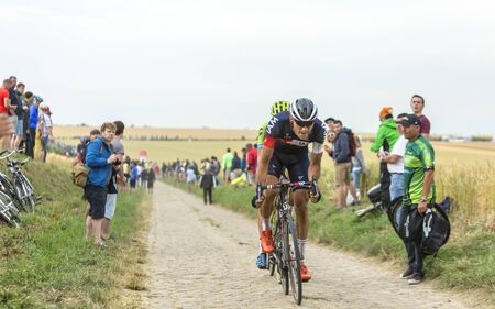 bystanders: Quievy,France - July 07, 2015: The Austrian cyclist Matthias Brandle of  IAM Cycling Team, inside the peloton, riding on a cobblestoned road during the stage 4 of Le Tour de France 2015 in Quievy, France, on 07 July,2015. Editorial
