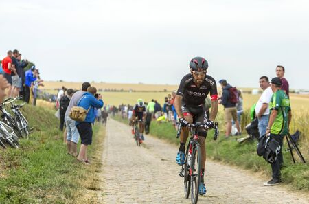 bystanders: Quievy,France - July 07, 2015: The Portuguese cyclist Jose Joao Mendes Pimenta Costa of Bora-Argon 18 Team, inside the peloton, riding on a cobblestoned road during the stage 4 of Le Tour de France 2015 in Quievy, France, on 07 July,2015. Editorial