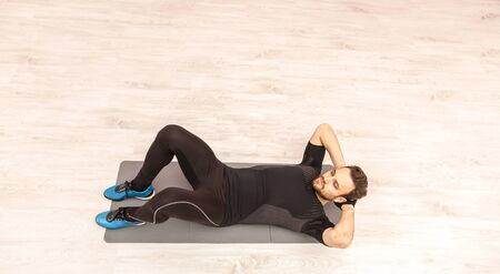 upper floor: Bird eye view of a young man doing sit-ups on the floor in a gym. Stock Photo