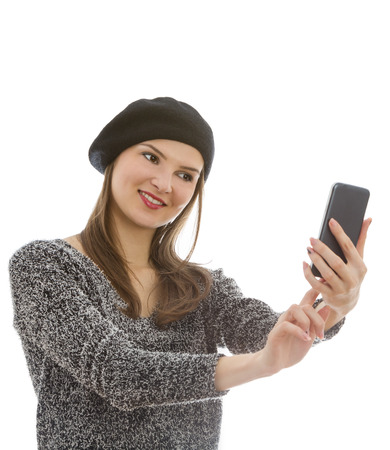 generation x: Young woman taking a selfie with a smartphone isolated against a white background.